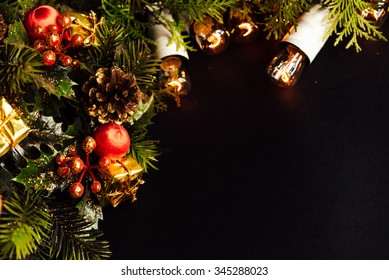 amazing beautiful green cedar wreath with cone and berry and christmas golden vintage garland lights on black background