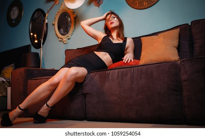 Amazing beautiful sexy girl with red lips resting on the couch. Concept of beauty and perfection interior. Attractive young woman in glasses and black dress sitting on black sofa. Fashion Photo