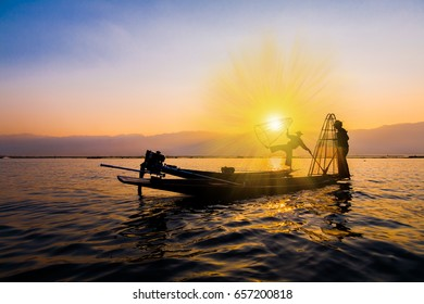 Amazing beautiful sunset in Inle lake. Inspiring landscape. Fantastic country Myanmar. Travel background. Wooden boats float. Unique sight