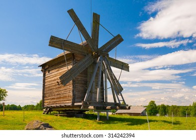 Amazing beautiful unique landscape. Old historical orthodox museum wooden mill Kizhi. Island Karelia Onega. North country Russia. Green grass in meadow. UNESCO world heritage. Rustic style