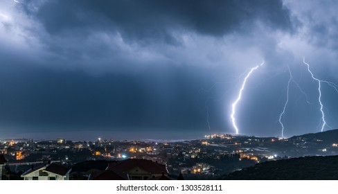 Amazing beautiful view of a lightning over night city, dramatic nighttime cityscape, stormy and overcast weather