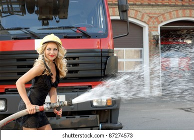 Amazing beautiful woman, holding a fire hose and wearing a helmet