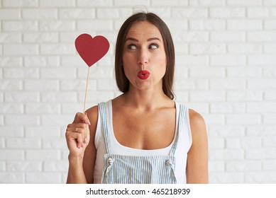 Amazing beautiful woman holding red paper heart and look at it, white brick wall on background