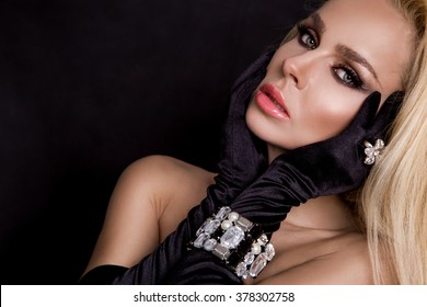 amazing beautiful young nude woman, model of elegant sexy blonde long hair in long gloves advertises jewelry, earrings and ring with crystals, diamonds, silver. gold covering her breasts with his hand