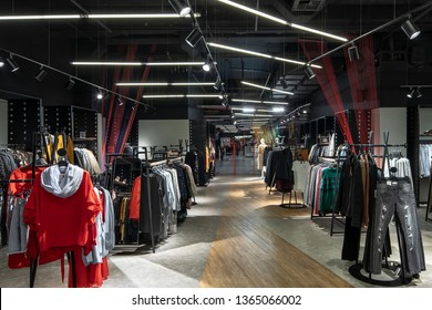 Amazing big clothing store with dark ceiling with hanging luminous lamps and multicolored ropes lines installations. There are many stands with hangers with different colorful clothes. Horizontal.