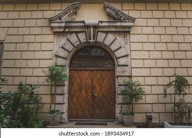 Amazing big old arched two-leaf wooden door with a mosaic window under a semicircular arch of stone. trees and bushes in pots at the entrance to the ancient building with stone wall in Krakow.