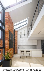 Amazing big windows in loft style apartment with white spacious kitchen, exposed red bricks on the walls and mezzanine