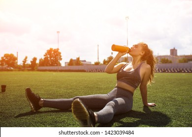 Amazing Blond in Sportwear Sitting on Big Football Field. Sportive Young Lady Drinks Water ar Sports Ground. Perfect Weather for Training