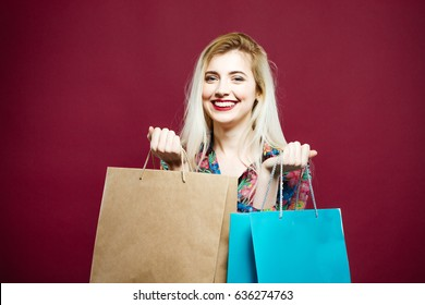 Amazing Blonde with Lond Hair and Charming Smile on Pink Background in Studio. Happy Woman Wearing Bright Shirt is Holding a Lot of Shopping Colorful Bags.
