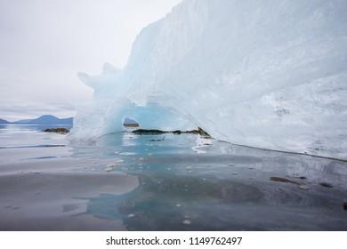 Amazing blue floating iceberg with grey skies behind