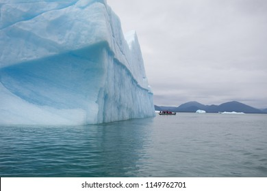 Amazing blue floating iceberg with grey skies behind and a small boat zodiac