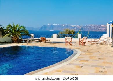 Amazing blue swimming pool on island of Santorini, Fira in Greece. Caldera view on a background.