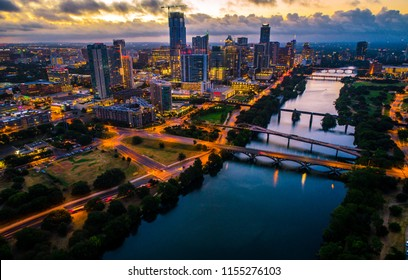 Amazing breathtaking aerial drone view above lit up city lights at night , nightscape of Austin , Texas Sunrise - Skyline Cityscape downtown office buildings glowing orange sunrise behind clouds