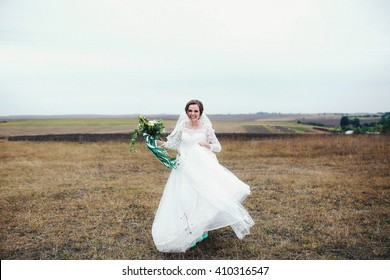 Amazing bride is holding her gown