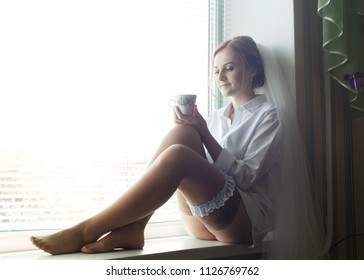 Amazing bride in the morning at home. Woman in white shirt and garter on leg with cup  sitting on the window.