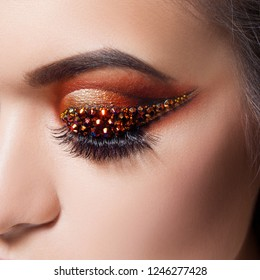 Amazing Bright eye makeup with a arrow with rhinestones. Brown and gold tones, colored eyeshadow. Close up