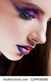Amazing Bright eye makeup in luxurious blue shades. Beautiful young woman with bright makeup, look down. Close up