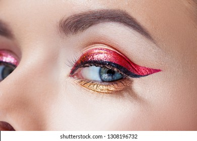 Amazing Bright eye makeup in luxurious red arrow. Red and gold shining tones, eye shadow. Close up