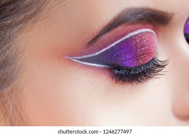 Amazing Bright eye makeup. Eye shadow with a purple tint and an unusual white arrow. Close up