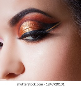 Amazing Bright eye makeup with a spectacular arrow. Brown and gold tones, colored eyeshadow. Close up