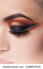 Amazing Bright eye makeup with a wide arrow. Brown and gold tones, colored eyeshadow. Close up