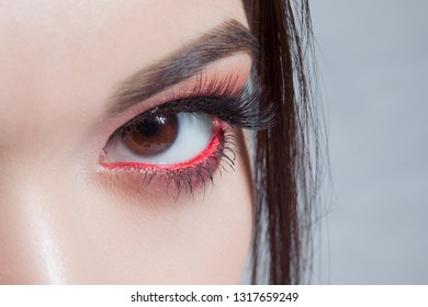 Amazing Bright eye makeup with a wide arrow. Brown and red tones, colored eyeshadow. Close up
