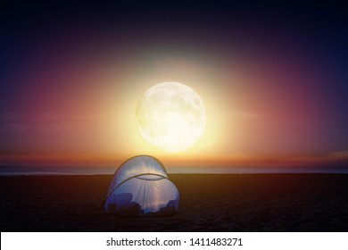 Amazing bright moon over the sea, beach and lit tent at sunrise