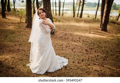 Amazing brunette bride with violet wedding bouquet at pine wood.