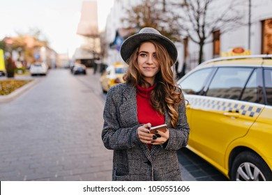 Amazing businesswoman in tweed coat walking down the road near yellow taxi. Glad long-haired woman in hat posing on the street, holding smartphone and looking with interest.