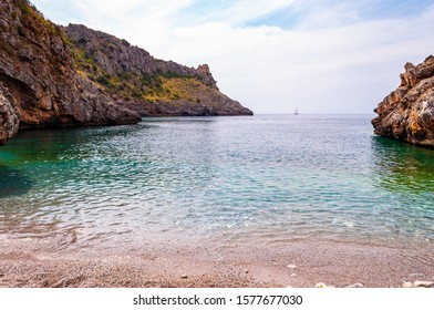 Amazing Cala Bianca beach surrounded by rocks and Tyrrhenian sea bay with crystal clear deep water full of underwater life. Sea yacht floating on Cala Bianca beach in Campania region in Italy