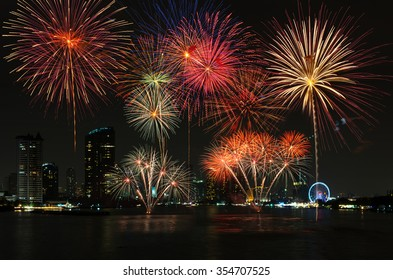 Amazing celebration fireworks over the river with bangkok cityscape soft focus background at night scene