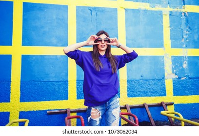 Amazing charming summer young woman with long hair in jeans and sunglasses having fun on striped yellow blue background.