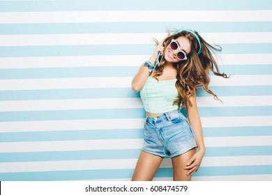 Amazing charming summer young woman with long brunette curly hair, in jeans shorts, sunglasses having fun on striped white blue background. Dancing, listening to music with headphones,. Place for text