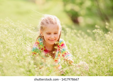 Amazing child resting at floral field full of green plants in colorful sweater in calm summertime