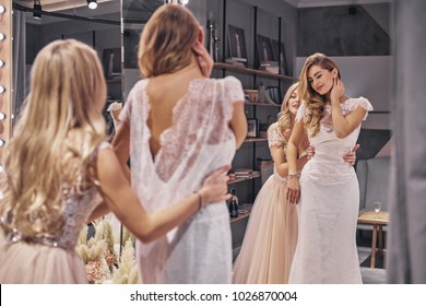 Amazing choice.  Reflection of attractive young woman adjusting a dress on her girlfriend while standing in the fitting room