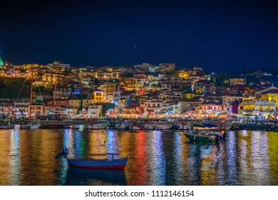 Amazing cityscape view of Parga city, Greece during the Summer. Long exposure HDR photography with beautiful architectural colorful buildings illuminated at night near the port of Parga Epirus, Greece