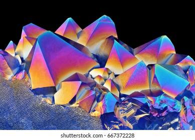 Amazing closeup of Blue Amethyst Quartz Rainbow Titanium Coating Aura Crystal cluster on black background. Macro of beautiful rare mineral stone