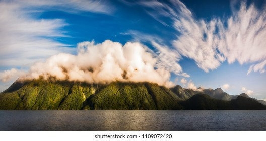 Amazing cloud formation raising over the mountain range at Lake Manapouri early in the morning on a beautiful summer day on a cruise to Doubtful Sound in New Zealand, South Island.