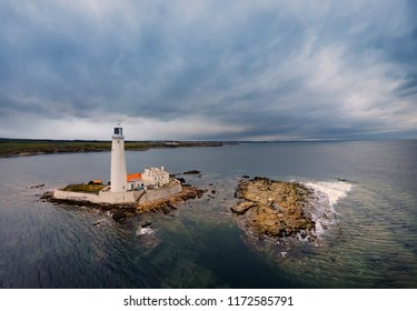 Amazing clouds above St. Mary's Lighthouse. Lighthouse and rocks during the tide. Whitley Bay, Northumberland, England. Great Britain. Main focus on Lighthouse and buildings. Drone photography