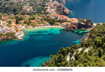 Amazing coastline with colorful houses under sunlight. Wonderful summer seascape with perfect blue sky of Ionian Sea. Assos village. Kefalonia. Greece. aerial shot.