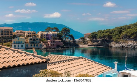 Amazing coastline with colorful houses under sunlight. Wonderful summer seascape with perfect blue sky of Ionian Sea. Assos village. Kefalonia. Greece