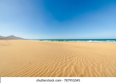 Amazing Cofete beach with endless horizon. Volcanic hills in the background and Atlantic Ocean. Cofete beach, Fuerteventura, Canary Islands, Spain.