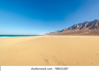 Amazing Cofete beach with endless horizon and traces on the sand. Volcanic hills in the background and Atlantic Ocean. Cofete beach, Fuerteventura, Canary Islands, Spain.