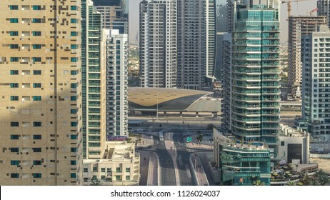 Amazing colorful dubai marina and JLT skyline during sunset timelapse. Great perspective of multiple tallest skyscrapers of the world with metro station. Sunlight over buildings. United Arab Emirates.