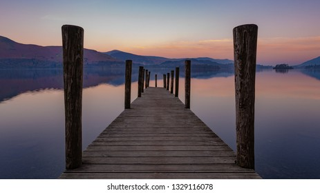 Amazing colorful sunrise on lake Derwentwater, in perspective view from aged wooden jetty, mountains reflecting in the background, Keswick, Lake District, England