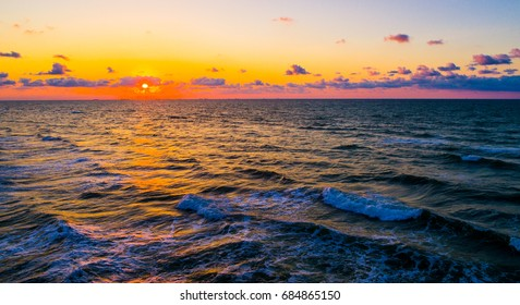Amazing Colorful Sunrise out over the waters of the Gulf of Mexico Open Water with Golden Hour colors aerial drone view Padre Island , Texas , USA