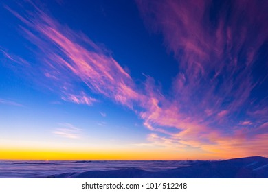 Amazing colorful sunset in mountains with absract wing shapes of clouds