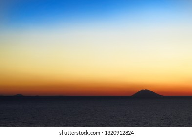 Amazing colorful sunset panorama with silhouette of volcano island Stromboli.Tropea, Italy