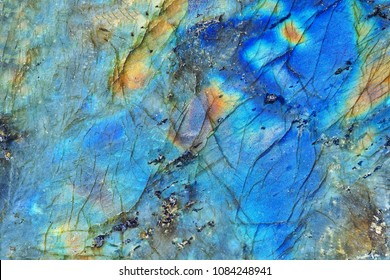 Amazing colorful texture of labradorite mineral gemstone background close-up. A nice natural blue and yellow background of pilished labradorite gemstone.