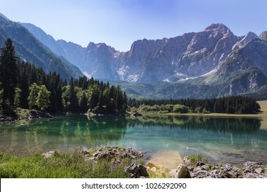 Amazing colors of alpine lakes Fusine park with mountains on background. Tarvisio, Friuli Venezia Giulia, Italy